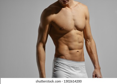 Cropped view of topless man in tight shorts