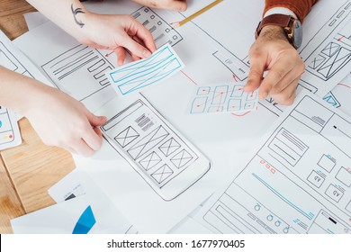 Cropped view of ux designers planning interface of mobile website with layouts on table