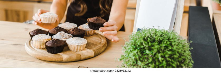 cropped view of waitress putting cupcakes on wooden tray in coffee house