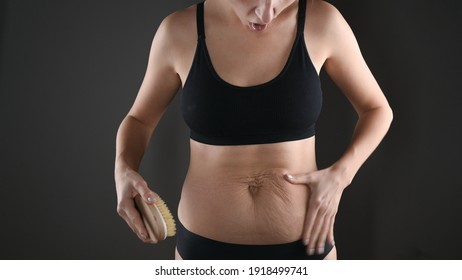 Cropped view of woman in bluck underwear massaging body, fat belly with wooden massage brush isolated on grey. Skin care and wight loss concept. High quality photo