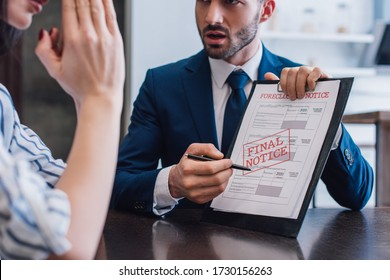 Cropped view of woman and collector pointing with pen at documents with foreclosure and final notice lettering at table