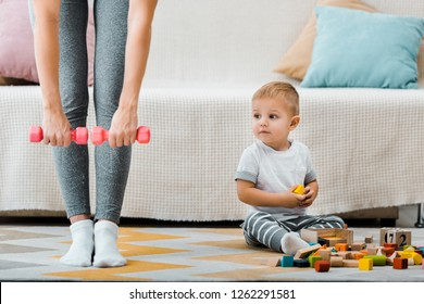 cropped view of woman doing fitness exercise with dumbbells and cute toddler boy sitting on carpet near multicolored cubes