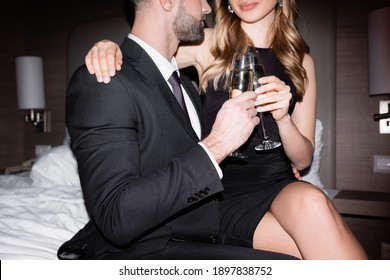 Cropped view of woman in dress holding glass of champagne and hugging boyfriend in suit on bed in hotel during night