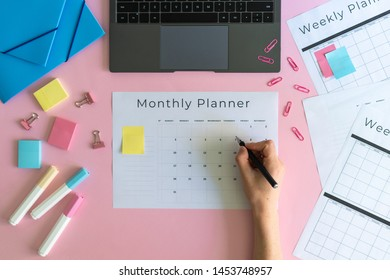 Cropped view of woman hand holding pen, writing notes in monthly planner with copy space on pastel pink background. Colorful stationery, laptop and folders on table