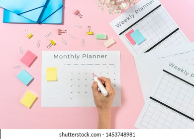 Cropped view of woman hand holding marker and writing notes in monthly planner with copy space on pastel pink background