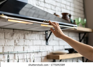 Cropped view of woman hand select mode on cooking hood, standing near kitchen appliance in contemporary interior with brick wall and decor on shelves at blurred background
