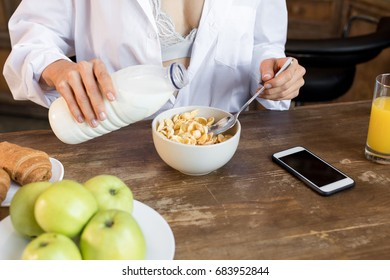 cropped view of woman having corn flakes with milk for breakfast in kitchen