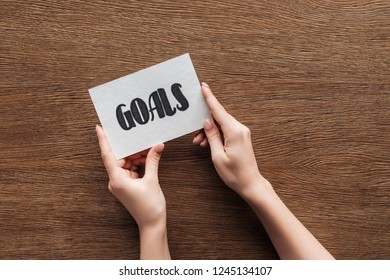cropped view of woman holding card with 'goals' lettering in hands on wooden background