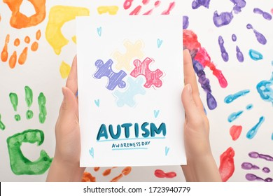 cropped view of woman holding card with Autism Awareness Day lettering and puzzle on white with hand prints