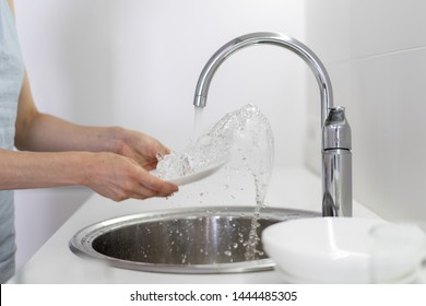 Cropped view of woman holding dishware in hands, washing plate in sink with water splash, standing on white bright kitchen