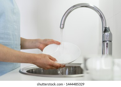 Cropped view of woman holding dishware in hands, washing plate under water in sink, standing on white bright kitchen