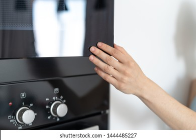 Cropped view of woman holding hand at black and opened door modern microwave oven, standing in kitchen