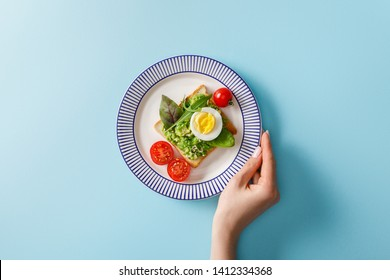 cropped view of woman holding ornamental plate with guacamole, boiled egg and greenery on toast near cherry tomatoes on blue background