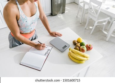 cropped view of woman holding pen near notebook with lettering and fruits