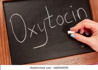 Cropped view of woman holding piece of chalk near blackboard with oxytocin lettering