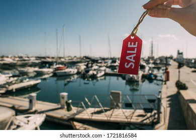 cropped view of woman holding red tag with sale lettering near docked yachts in mediterranean sea