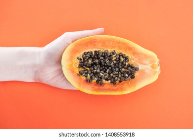 cropped view of woman holding ripe exotic papaya half with black seeds isolated on orange