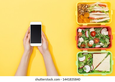 cropped view of woman holding smartphone near lunch boxes with food
