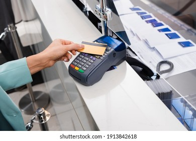 Cropped view of woman paying with credit card and payment terminal in hotel