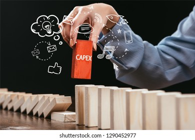 cropped view of woman picking red block with word 'capex' out of wooden bricks, icons on foreground