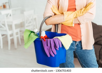 Cropped view of woman in rubber gloves holding bucket with cleaning supplies