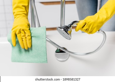 Cropped view of woman in rubber gloves holding shower and rag in bathroom on blurred background