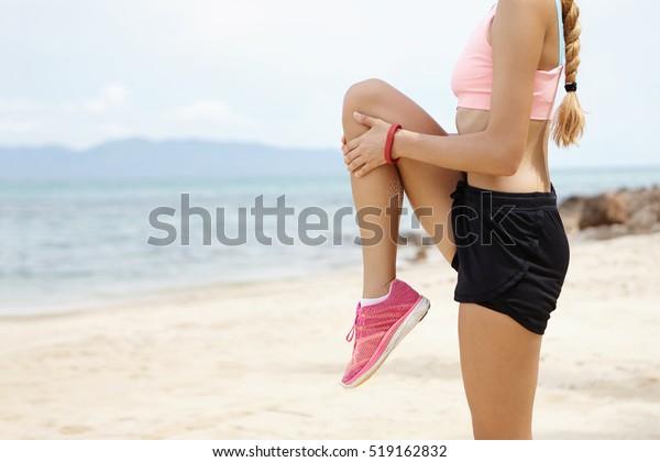 Bewachte Sicht auf die Frau Läufer, die Warmup-Routine am Strand vor dem Laufen, Stretching Muskeln, die stehende einzelne Knie-zu-Brust-Stretch. Sportlerin, die Beine für das Cardio-Training vorbereitet
