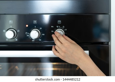 Cropped view of woman select program turning switch at modern built in oven, select program, standing in kitchen
