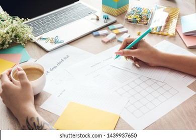 cropped view of woman sitting with cup of coffee behind wooden table with stationery and laptop and writing in notes planners