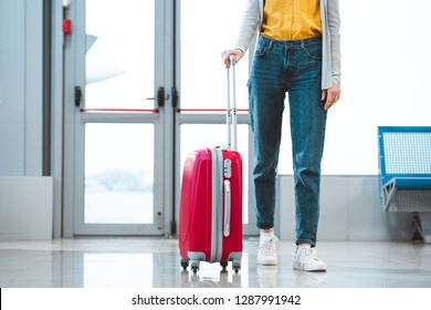 cropped view of woman standing with baggage in airport