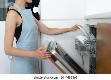 Cropped view of woman standing on kitchen near built in, opened and modern dishwasher machine, holding clean plate in hand