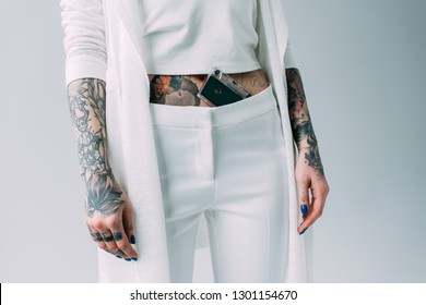 cropped view of woman with tattoos standing with audio tape in pants isolated on grey
