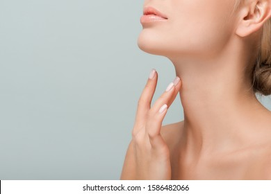 cropped view of woman touching neck isolated on grey