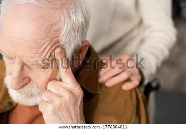 cropped view of woman touching shoulder of husband, sick on dementia, sitting with closed eyes and touching head