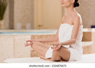 cropped view of woman in towel meditating at spa