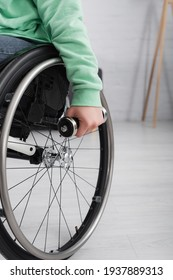 Cropped view of woman in wheelchair holding dumbbell at home