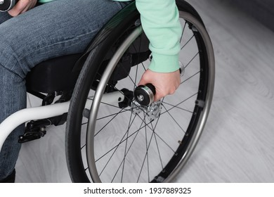 Cropped view of woman in wheelchair holding dumbbell