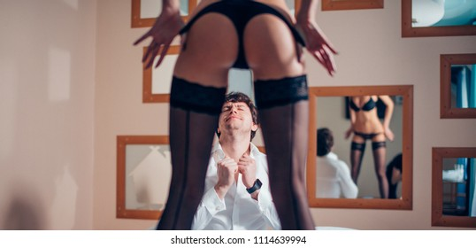 Cropped view of womans buttocks in underwear standing in front of amased guy lying in bed at the hotel. Emotional face of excited delighted man in focus