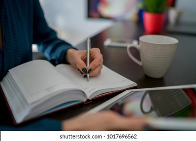 Cropped view of woman's hand with pen writing notes in notebook,calculations of personal budget in order to save. Selective focus on pages,female student taking information from network while studying