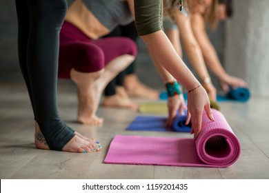 Cropped view of women hands unrolling colourful yoga mats before practicing yoga, preparing for exercise in studio interior