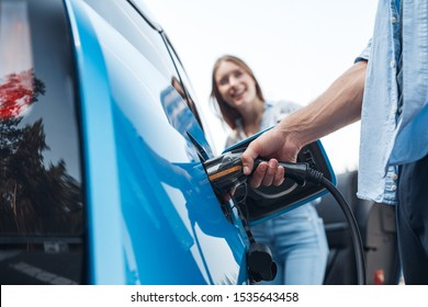 Cropped view of young adult man holding power cable supply plugged in electric car, charging automobile battery from small public station. Happy girl standing on blurred background with smile