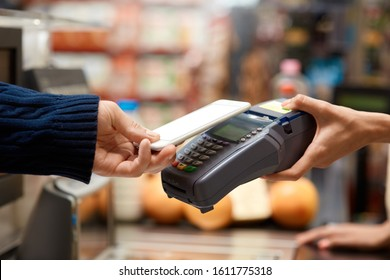 Cropped view of young adult man standing on checkout, paying for shopping in grocery store, using modern smartphone while cashier holding terminal in hand