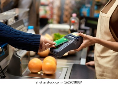 Cropped view of young adult man holding plastic credit card in hand, using terminal and paying for shopping in supermarket