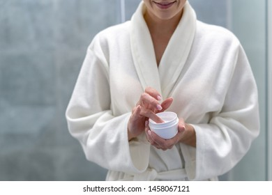 Cropped view of young adult woman in bathrobe holding jar with cream in hands, standing at bathroom with copy space