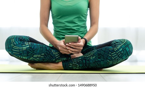 Cropped view of young adult woman sitting on fitness mat and holding online app in smartphone after training at home