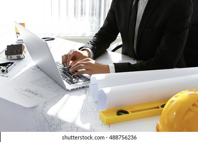 Cropped view of young Caucasian engineer wearing formal suit working on construction project using laptop computer, sitting at office desk, surrounded with engineering tools and rolls of blueprints