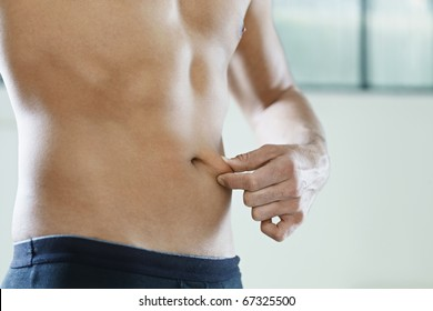 cropped view of young caucasian man measuring fat on belly. Horizontal shape, mid section, side view, copy space