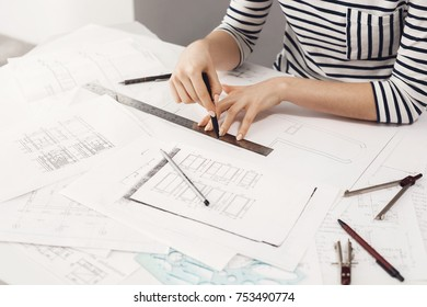 Cropped view of young good-looking female designer wearing stripes outfit, sitting at comfy light work place, working on new design project using pen, ruler and paper