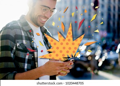 Cropped view young hipster guy receives discounts notification on smartphone with surprise infographics elements effect. Cheerful male reading text message on cellular while standing on city street