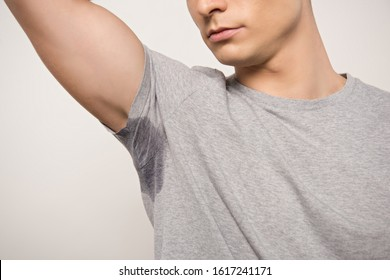cropped view of young man in grey t-shirt with sweaty underarm isolated on grey